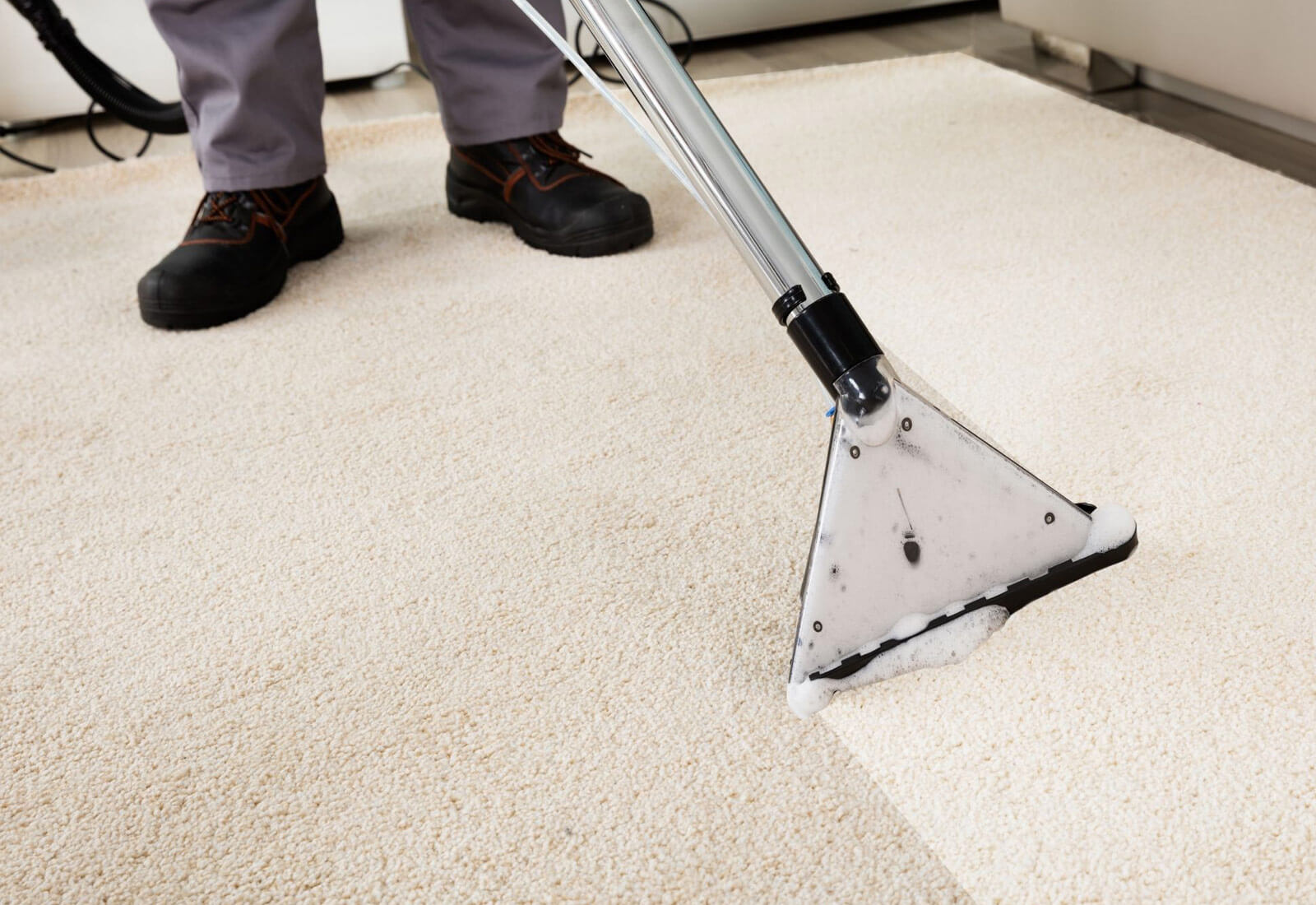 A man steam cleaning the carpet
